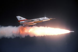 An air-to-air right side view of an F-106 Delta Dart aircraft after firing an ATR-2A missile over a range. An auxiliary fuel tank is on each wing. The aircraft is assigned to the 194th Fighter Interceptor Squadron, California Air National Guard.