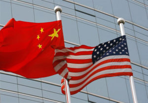 "A US and a Chinese flag wave outside a commercial building in Beijing, 09 July 2007. US Secretary of State Condoleezza Rice 06 July 2007 accused China of flouting the rules of global trade in its headlong economic expansion as the US administration ""has not been hesitant"" to deploy trade tools against China, including a complaint lodged with the World Trade Organization over copyright piracy. AFP PHOTO/TEH ENG KOON"